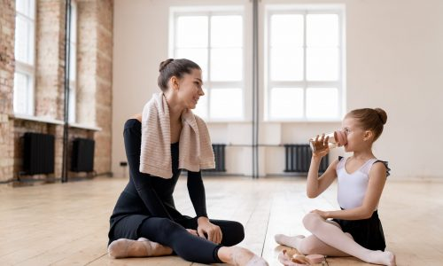 Two,Ballerinas,Sitting,On,The,Floor,After,Training,And,Discussing